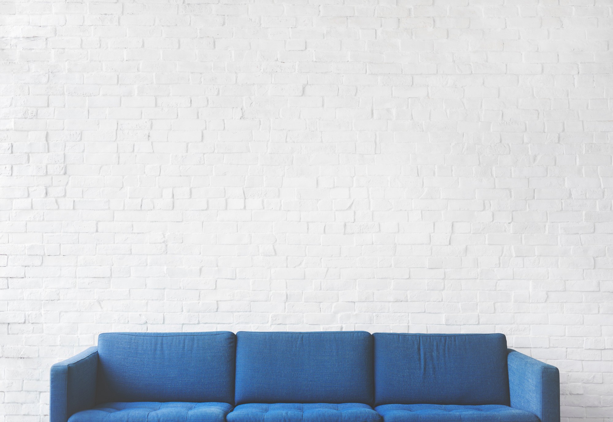 Blue Couch in front of white brick wall.